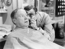 Barberare som ser en mans framsida till och med ett förstoringsglas (alla visade personer inte är längre uppehälle, och inget god Arkivbild