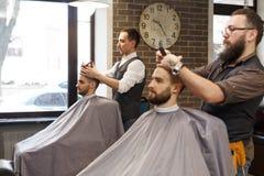 Barberare som utformar skägget med sax till klienten på frisersalongen Royaltyfri Bild