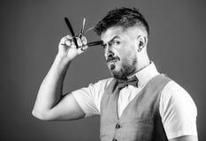 Barberarehemligheter Barberare som rymmer tappningbarberarehj?lpmedel Sk?ggig man med rakkniven och sax i retro frisersalong hips royaltyfri fotografi