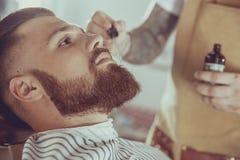 Barberaren applicerar skäggoljan med en droppglass royaltyfria foton