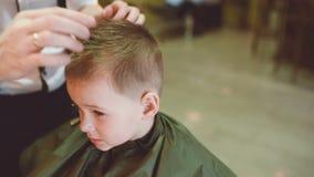 Barberaren gör en frisyr för roligt behandla som ett barn lite pojken stock video