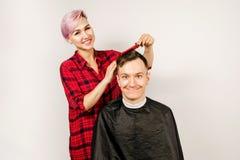Barberaren klippte hår, hårkammen och den unga mannen för rakningar på en vit bakgrund Nära övre stående av en grabb och en flick arkivfoton