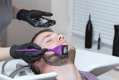 Barberaren målar skägget och mustaschen av den unga mannen i frisersalongen royaltyfri bild