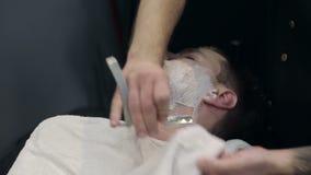 Barberaren rakar skägget av klienten i frisersalongen lager videofilmer