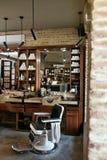 Barberaren shoppar inre Salong för manskönhethår med antik stol Arkivfoto