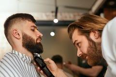 Barberaren shoppar Mannen får skägghår för att klippa royaltyfria foton