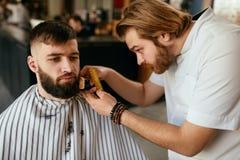 Barberaren shoppar Mannen får skägghår för att klippa arkivfoton