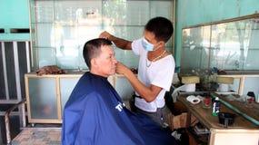 Barberaren som har en frisyr för gäst Royaltyfria Bilder