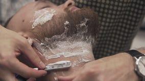 Barberaren som rakar den skäggiga mannen med den raka rakkniven i barberare, shoppar i ultrarapid arkivfilmer