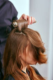 Barberaren torkar håret med hårtorken av barn, härlig flicka i en skönhetsalong arkivbilder