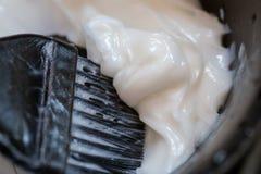 Barberaretillförsel som applicerar färgkräm på hår i salong royaltyfria foton