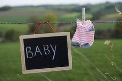 Chalk board with text BABY and socks hanging on barbed wire stock photos