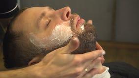 Barberman genom att använda mjuk kräm på framsida av mannen med skägget arkivfilmer