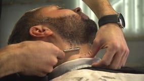 Barberman het scheren baard van de mens stock video
