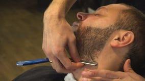Barberman het scheren baard van de mens stock videobeelden