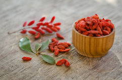 Barberries and goji berries on wooden background. Barberries near goji berries heap and wooden bowl with goji  on wooden background Royalty Free Stock Photo