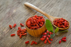 Barberries and goji berries on wooden background. Barberries near goji berries heap and wooden spoon, bowl with goji  on wooden background Royalty Free Stock Photos