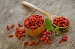Barberries and goji berries on wooden background Stock Images