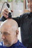 Barbers Shaving Senior Mans huvud Royaltyfria Bilder