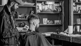 Barbershop concept. Hipster bearded client got hairstyle. Barber with hairdryer works on hairstyle for bearded man royalty free stock photography