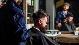 Barbershop concept. Man with beard covered with black cape sits in hairdressers chair, mirror background. Hipster with stock photos