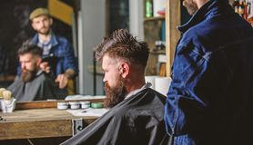 Barbershop concept. Man with beard covered with black cape sits in hairdressers chair, mirror background. Hipster with stock images