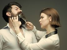 Barbershop or hairdresser concept. Woman hairdresser cuts beard with scissors. Guy with modern hairstyle visiting stock image