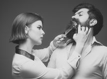 Barbershop or hairdresser concept. Woman hairdresser cuts beard with scissors. Guy with modern hairstyle visiting Royalty Free Stock Image