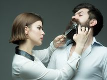 Barbershop or hairdresser concept. Woman hairdresser cuts beard with scissors. Guy with modern hairstyle visiting Royalty Free Stock Photo