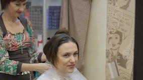 Barbershop. Harboring girl brunette protective cloak before hair dyeing procedure and eyebrow stylist master. stock video