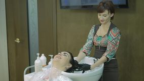 barbershop hoofd, zijaanzicht de vrouw wast de verf met lang zwart haar Mooi meisje met een verf op de cliënt ` s stock video