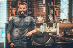 Barbershop owner. Cheerful young bearded man looking at camera and holding hand in pocket while leaning on chair at barbershop royalty free stock photos