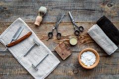 barbershop ` Rapagem e corte de cabelo de s dos homens Escova, lâmina, espuma, sciccors na opinião superior do fundo de madeira d fotografia de stock