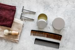 At the barbershop. Razors, shaving brush, comb, wax, towel on grey background top view Stock Photos