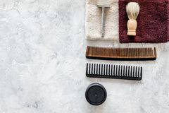 At the barbershop. Razors, shaving brush, comb, wax, towel on grey background top view copyspace Royalty Free Stock Photo