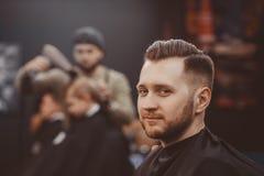 barbershop Uomo con la barba nel negozio di barbiere Salone di capelli moderno fotografia stock libera da diritti