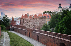 Barbican - Fortified medieval outpost and city wall in sunset in the historic center of Warsaw, Poland Stock Image