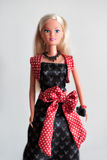 Barbie doll in evening wear with a red sash. Barbie doll with long blond hair in evening wear with a red sash carrying a purse  on grey Stock Images