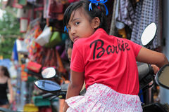 Barbie Girl in Ubud. BALI, INDONESIA, August 12, 2014 : A barbie girl rides a motorbike in the market streets of Ubud royalty free stock photography