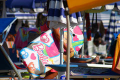 Barbie. Surfboard being held by a young girl at the beach in Le Marche Italy. Shot with a Canon 35mm using a 200mm stock image