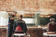 Barbiere alla moda che dà taglio di capelli al cliente fotografie stock