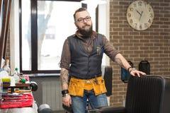 Barbiere barbuto che posa alla macchina fotografica al parrucchiere immagine stock libera da diritti