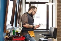 Barbiere barbuto che posa alla macchina fotografica al parrucchiere fotografia stock