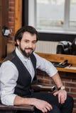 barbiere bello che si siede sulla sedia al posto di lavoro ed allo sguardo fotografie stock libere da diritti