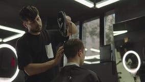 Barbiere che asciuga capelli maschii nel salone di lavoro di parrucchiere Colpo tenuto in mano 4K stock footage