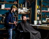 Barbiere che disegna capelli del cliente barbuto con il pettine ed il tagliatore Cliente dei pantaloni a vita bassa che ottiene t immagini stock libere da diritti