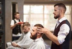 Barbiere che esamina specchio su capelli del cliente prima del taglio di capelli immagini stock libere da diritti