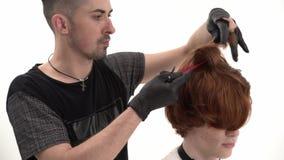 Barbiere che esegue un taglio di capelli per il suo cliente con i capelli dello zenzero, il pettine holsing e le forbici stock footage