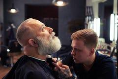 Barbiere che fa taglio di capelli all'uomo senior attraente bello fotografie stock