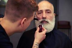Barbiere che fa taglio di capelli all'uomo senior attraente bello con il bea immagini stock